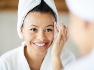 Head and shoulders portrait of smiling Mixed-Race woman applying face cream during morning routine