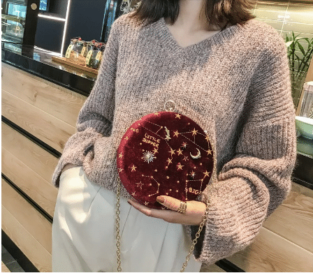 barrel shaped purse with stars, moon, and constellation embroidery.