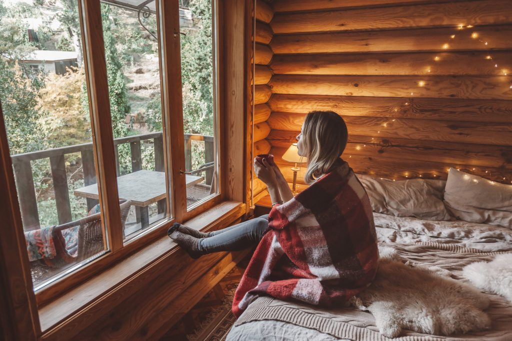 woman wrapped in blanket looking out the windows of her tiny home