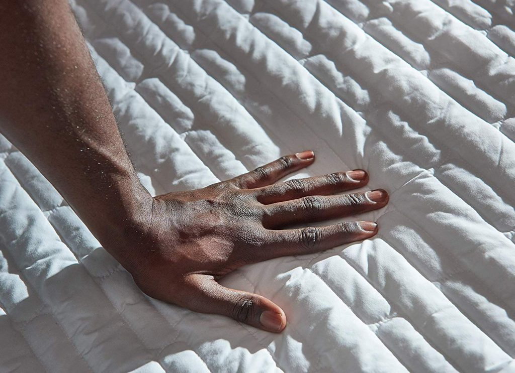 a woman's hand running over the Chilipad mattress