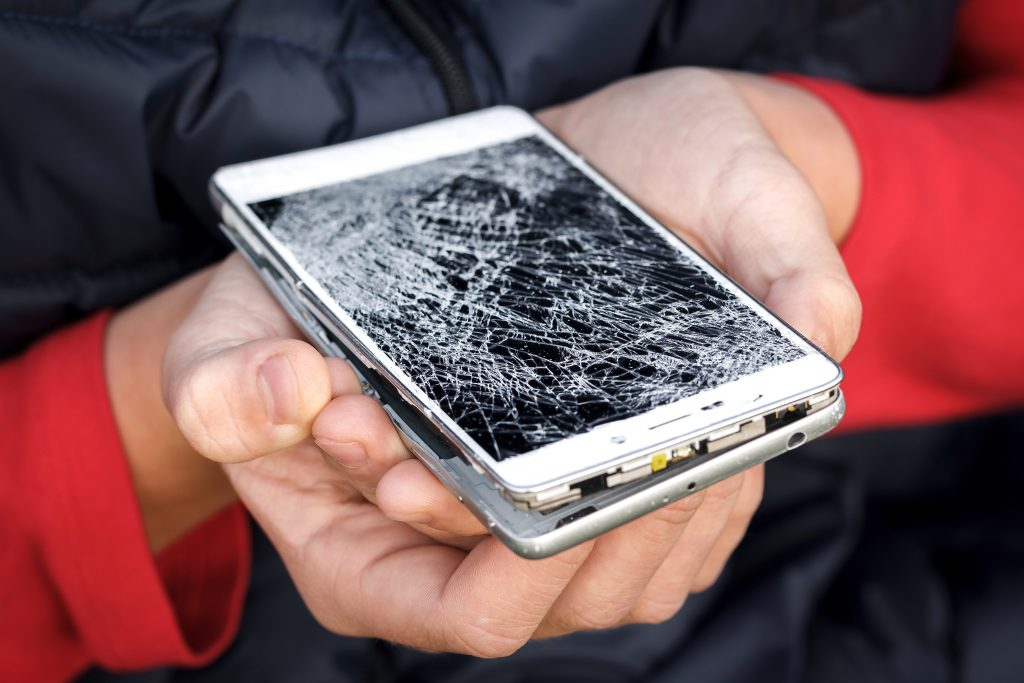 hands holding shattered phone case
